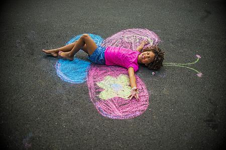 小女孩躺在粉笔蝴蝶翅膀之间的地板上图片