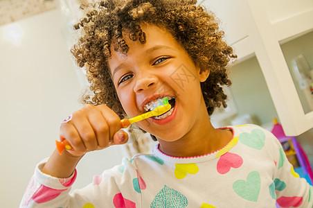 在浴室刷牙的微笑女孩的肖像图片