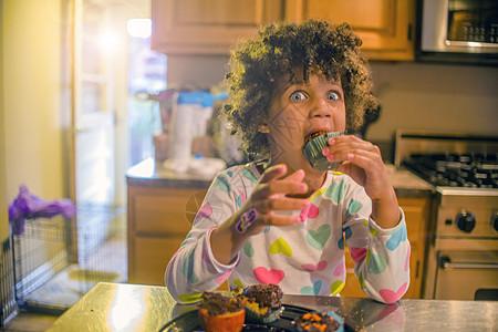 在厨房柜台吃纸杯蛋糕的惊讶女孩的肖像图片