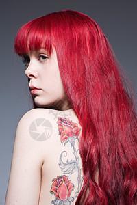 红色长发纹身的年轻女子图片