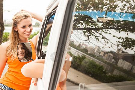在里约热内卢的露营车窗口交谈的年轻女性图片