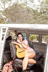 在里约热内卢的露营车上带吉他的年轻女子图片