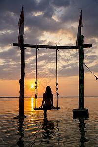印度尼西亚秋千上观看日落的女性游客剪影图片