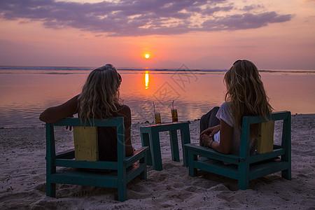 印度尼西亚观看海上日落的女性游客剪影图片