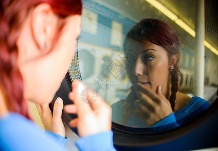 洗衣店里的年轻女人看着洗衣机里的倒影图片