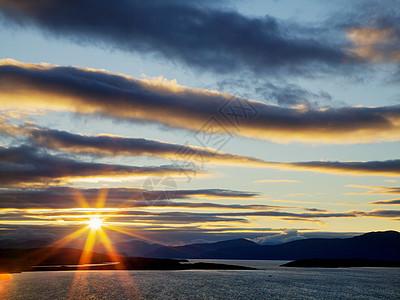 在英国苏格兰西北高地的群山上,阳光穿过戏剧性的风暴云图片