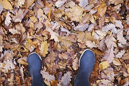 穿胶靴的女人在秋叶堆中图片