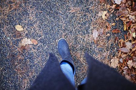 穿胶靴的女人在秋叶中漫步图片