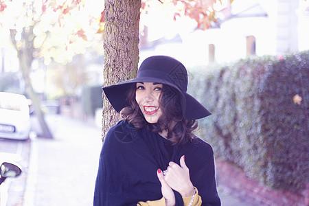 戴黑帽子披风的年轻女子图片