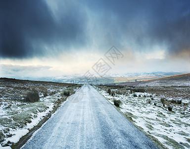 英国约克郡斯韦莱德尔,前方有暴风云的结冰乡村道路图片