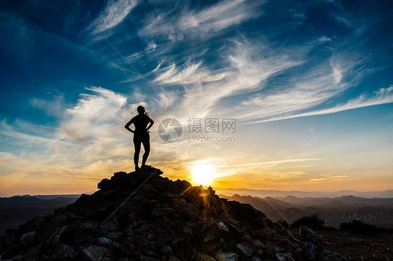 美国加利福尼亚州Joshua Tree国家公园Ryan Mountain徒步旅行小径日落时分站在山顶的中年妇女剪影图片