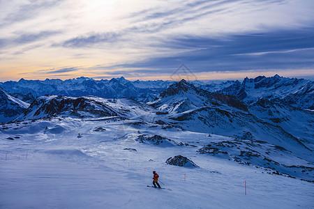 黄昏时在山上滑雪者,西尼亚,意大利图片