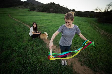 站在田里解开丝带的年轻女子图片