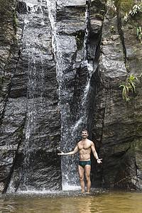 巴西里约热内卢蒂华卡森林瀑布前张开双臂的成年男子肖像图片