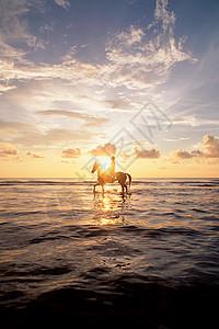 日落时在海上骑马的人图片