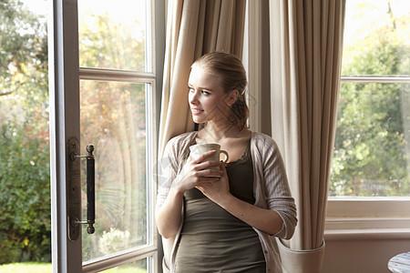 拿着酒杯望向窗外的女子图片