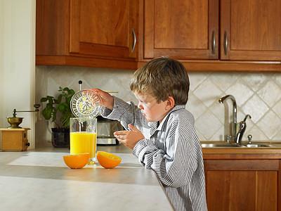 小男孩在厨房里做橙汁图片