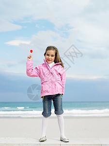 海边抱棒棒糖的小女孩图片