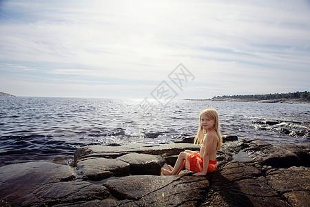 坐在湖边岩石上的男孩图片