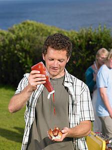 把番茄酱倒在热狗上的人图片