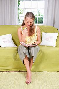 在沙发上看书的年轻女人图片