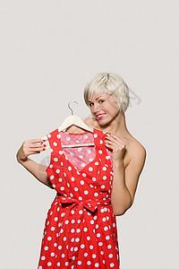 拿着连衣裙的年轻女子图片
