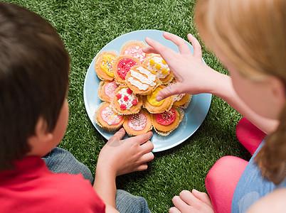 在聚会上吃蛋糕的男孩和女孩图片