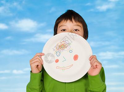 一个男孩拿着一个上面画着一幅图画的纸盘图片