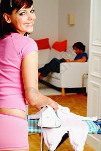 年轻母亲高兴地熨衣服图片