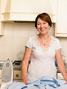 在厨房熨衣服的女人图片