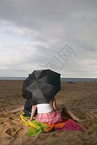 海滩上打伞的情侣图片