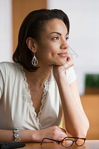 坐在桌旁沉思的女人图片