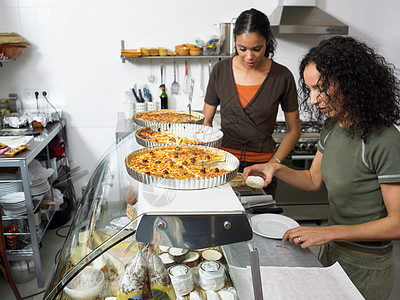 在熟食店厨房准备食物的女人图片