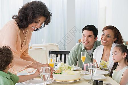 女人和家人一起切蛋糕图片