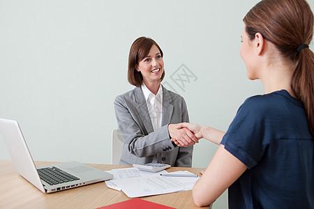 年轻女子与财务顾问握手图片