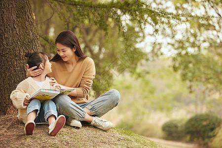 温馨母女坐在树下读书图片