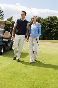 在高尔夫球道上散步的情侣图片