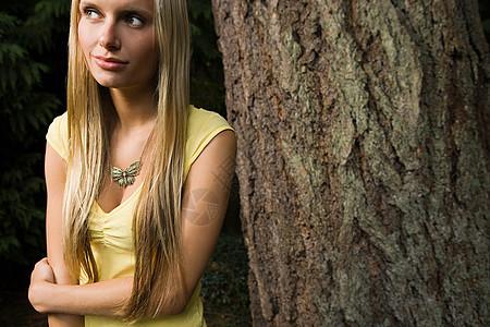 靠在树旁的年轻女子图片
