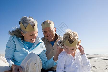祖父母和孙女在海滩上戴着纸制皇冠图片