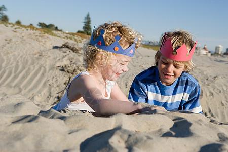 孩子们戴着纸冠在海滩上玩耍图片