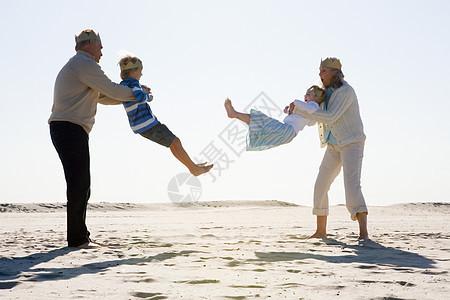 祖父母和孙子在海滩上玩耍图片