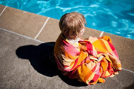 男孩裹着毛巾坐在池边图片