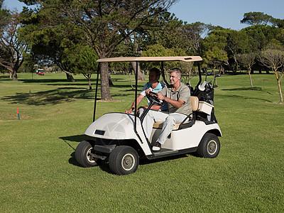 两个成熟的男子在高尔夫球场的高尔夫球车上图片
