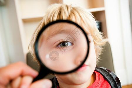 小男孩透过放大镜看照相机图片