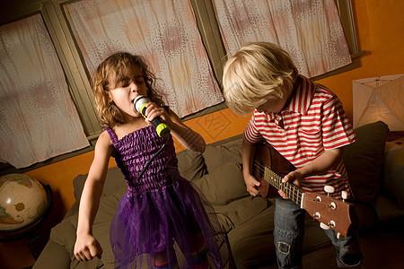 女孩用麦克风唱歌,男孩弹吉他图片