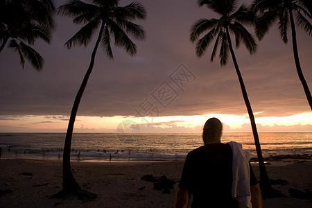 日落时海滩上的男人图片