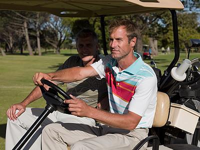 两个成熟的男子在高尔夫球场开车图片