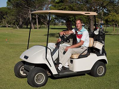 两个中年男性在高尔夫球场的高尔夫球车上图片