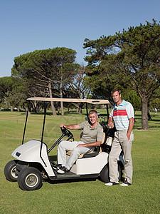 两个男子在高尔夫球场的高尔夫球车上图片