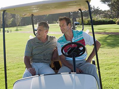 两个中年的男子坐在高尔夫车上图片